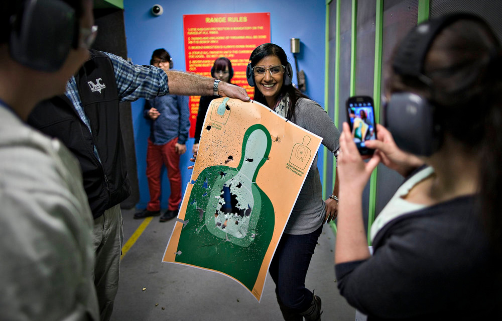 . Mona Kambo (C) holds up her shooting target while her friend Kylie Cronin (R) takes a picture at the DVC Indoor Shooting Centre in Port Coquitlam, British Columbia March 22, 2013. The DVC is the only indoor shooting centre in the province that rents firearms to the public without a license. Friday night is \'Ladies Night\' at the centre. Canada has very strict laws controlling the use of handguns and violent crime is relatively rare. Picture taken March 22, 2013.    REUTERS/Andy Clark