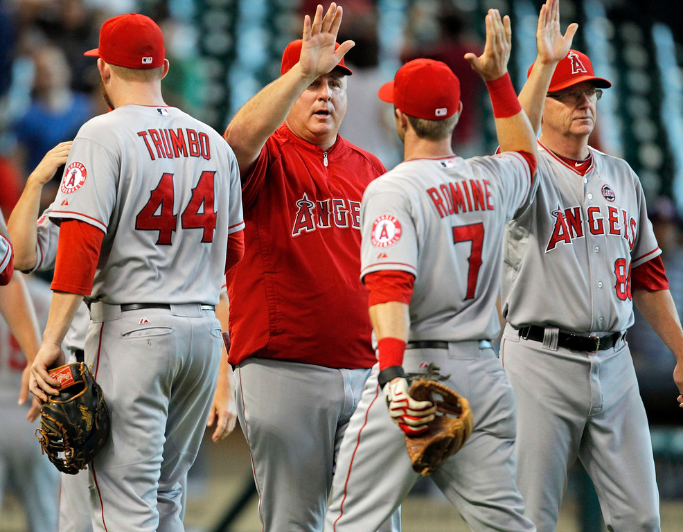. Los Angeles Angels manager Mike Scioscia, center, celebrates Andrew Romine (7) after the Angels 2-1 victory over the Houston Astros in a baseball game Sunday, Sept. 15, 2013, at Minute Maid Park in Houston. (AP Photo/Eric Christian Smith)