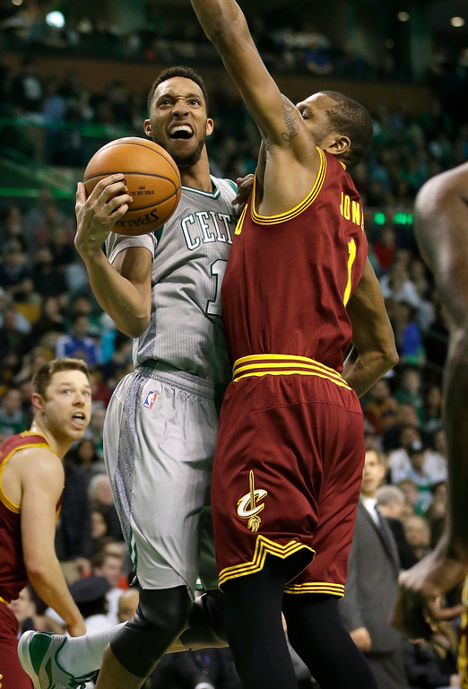 . Boston Celtics guard Evan Turner (11), left, tries to take a shot as Cleveland Cavaliers forward James Jones (1) reaches to block him during the second quarter of an NBA basketball game, Sunday, April 12, 2015, in Boston. (AP Photo/Steven Senne)