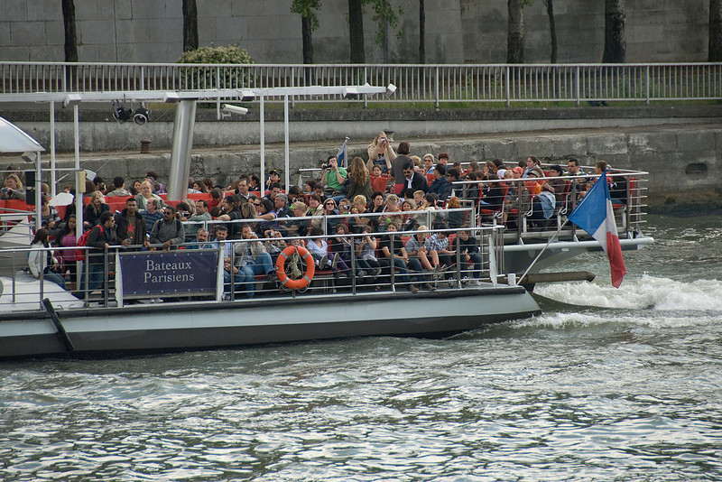 Tourists on a boat cruising over Seine River - Paris, France