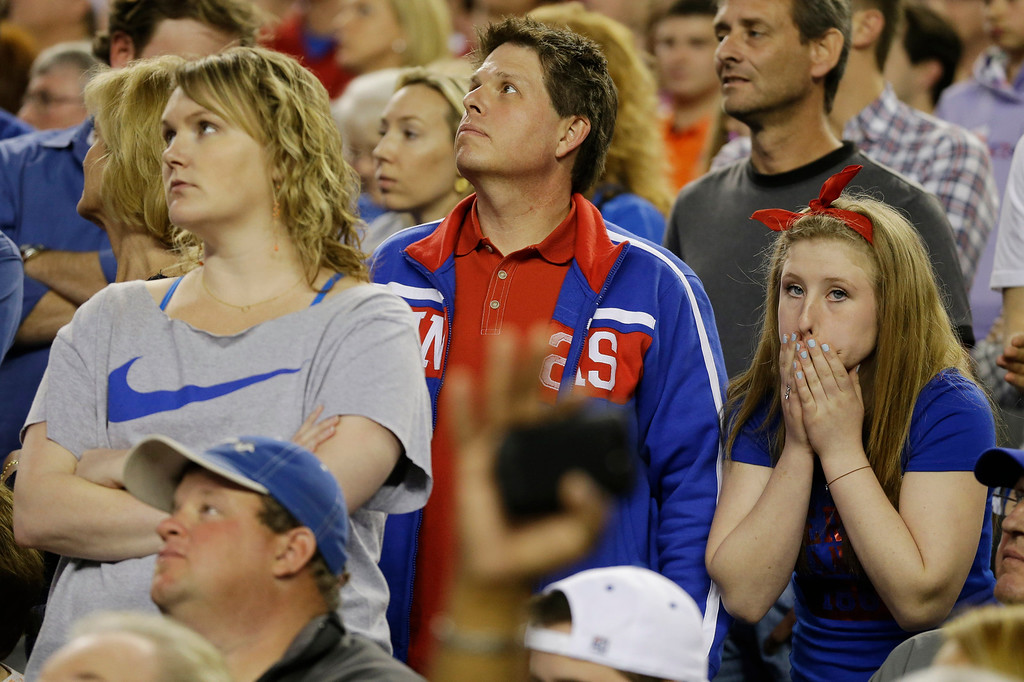. Kansas  fans react in the during overtime of a regional semifinal game against Michigan in the NCAA college basketball tournament, Friday, March 29, 2013, in Arlington, Texas. (AP Photo/Tony Gutierrez)
