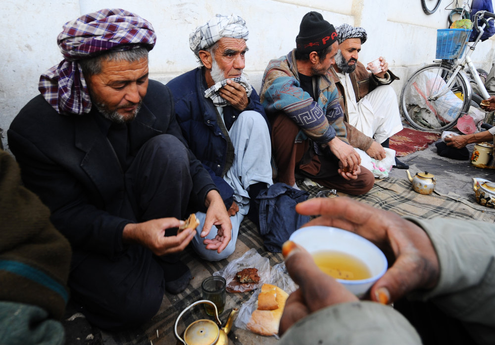 Description of . Afghan men labourers sit on the ground to drink tea in Mazar-i-Sharif in Balkh province on December 22, 2012. Once known as the