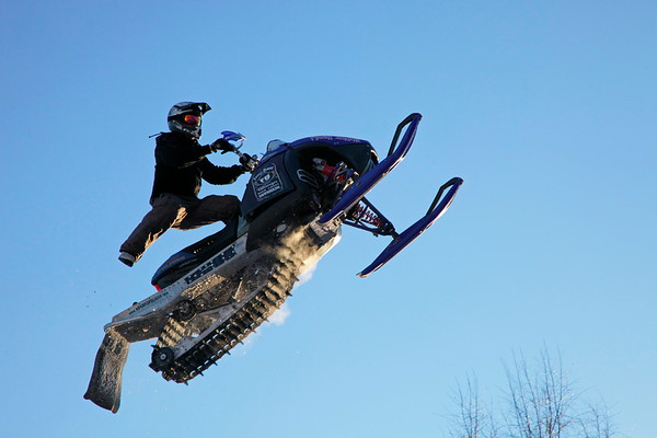 Snow mobile artist flying through the air