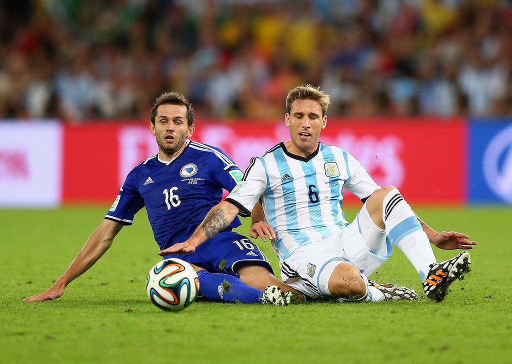 . Senad Lulic of Bosnia and Herzegovina and Lucas Biglia of Argentina battle for the ball during the 2014 FIFA World Cup Brazil Group F match between Argentina and Bosnia-Herzegovina at Maracana on June 15, 2014 in Rio de Janeiro, Brazil.  (Photo by Jamie Squire/Getty Images)