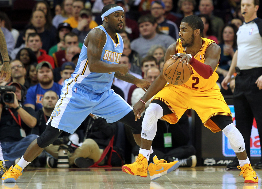 . Cleveland Cavaliers Kyrie Irving is defended by Denver Nuggets Ty Lawson (L) during the second quarter of their NBA basketball game in Cleveland, February 9, 2013.   REUTERS/Aaron Josefczyk