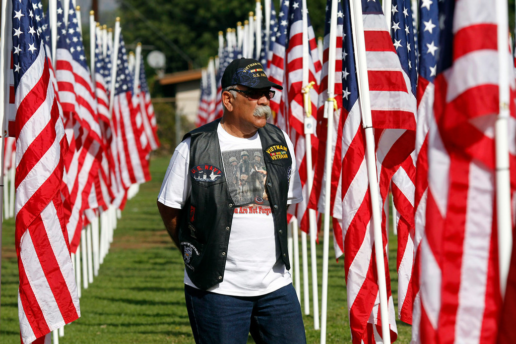 . Nick Silva, Vietnam Veteran from Covina, stands next to a flag he dedicated for a friend, during the opening ceremony for the Field of Valor, where 2,027 flags are posted in honor of Veterans Day, at the Field of Valor, at Sierra Vista Middle School in Covina, CA., Sunday, November 10, 2013. (Photo by James Carbone for the San Gabriel Valley Tribune)