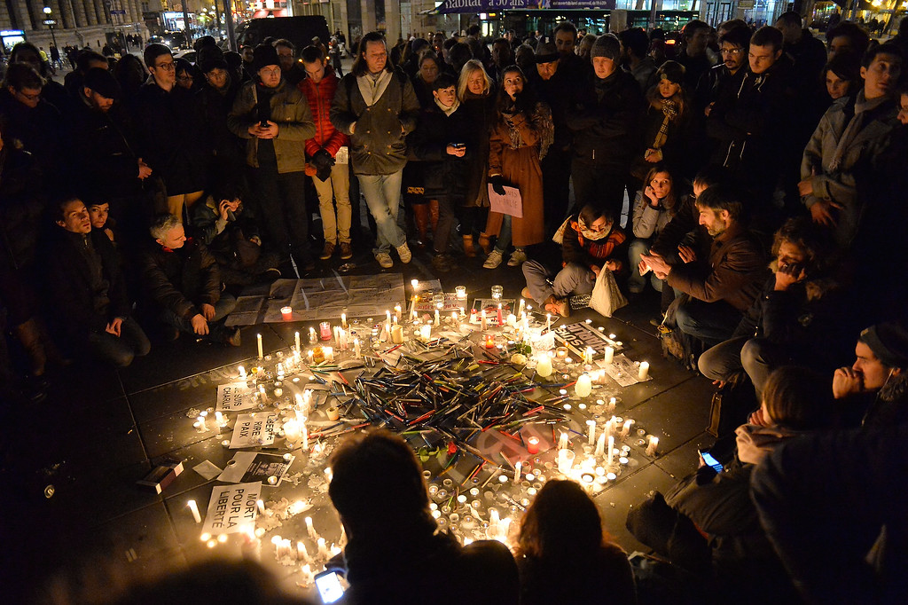 . PARIS, FRANCE - JANUARY 07:  People gather around candles and pens at the Place de la Republique (Republic square) in support of the victims after the terrorist attack earlier today on January 7, 2015 in Paris, France. Twelve people were killed, including two police officers, as two gunmen opened fire at the offices of the French satirical publication Charlie Hebdo.  (Photo by Aurelien Meunier/Getty Images)