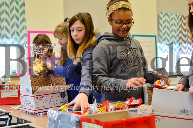 From left, Abby Fleeger, Julie Demeio, Madie Krainbucher and Kiki Shadd pack snacks into boxes for soldiers stationed in the Middle East on Nov. 30, 2018. The girls are sixth graders at Butler Middle School. Tanner Cole/Butler Eagle