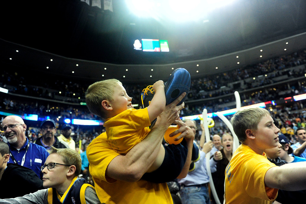 . DENVER, CO - APRIL 14: A young fan comes away with on of JaVale McGee\'s, (34) of the Denver Nuggets, shoes the second half of action. The Denver Nuggets defeat the Portland Trail Blazers 118-109 at the Pepsi Center. (Photo by AAron Ontiveroz/The Denver Post)