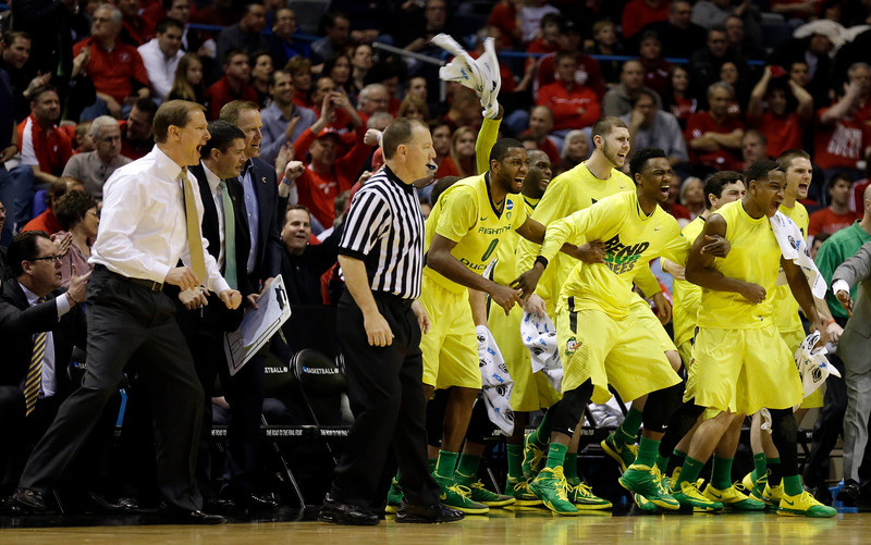 . Oregon bench celebrate after Joseph Young (3) shoots a three pointer during the second half of a second-round game in the NCAA college basketball tournament Thursday, March 20, 2014, in Milwaukee. (AP Photo/Jeffrey Phelps)