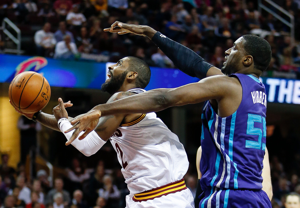 . Cleveland Cavaliers\' Kyrie Irving, left, goes up for a shot after being fouled by Charlotte Hornets\' Roy Hibbert (55) during the first half of an NBA basketball game Sunday, Nov. 13, 2016, in Cleveland. (AP Photo/Ron Schwane)