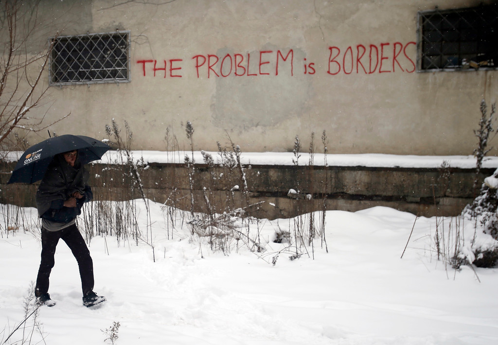 . A migrant walks in front of an abandoned warehouse in Belgrade, Serbia, Wednesday, Jan. 11, 2017. Hundreds of migrants are sleeping rough in parks and make-shift shelters in the Serbian capital in freezing temperatures waiting for a chance to move forward toward the European Union. (AP Photo/Darko Vojinovic)