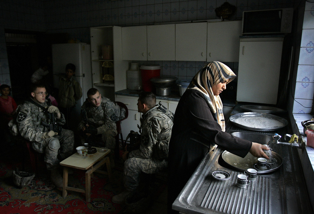 . An Iraqi woman washes dishes as US soldiers from Baker Company 2-12 Infantry Battalion temporarily occupy her home during a patrol in the Dora neighborhood of southern Baghdad, 16 March 2007. Shiite protesters demanded the removal of a US military base from Sadr City in east Baghdad as US commanders reported a surge of attacks on troops in a province near the capital. (DAVID FURST/AFP/Getty Images)