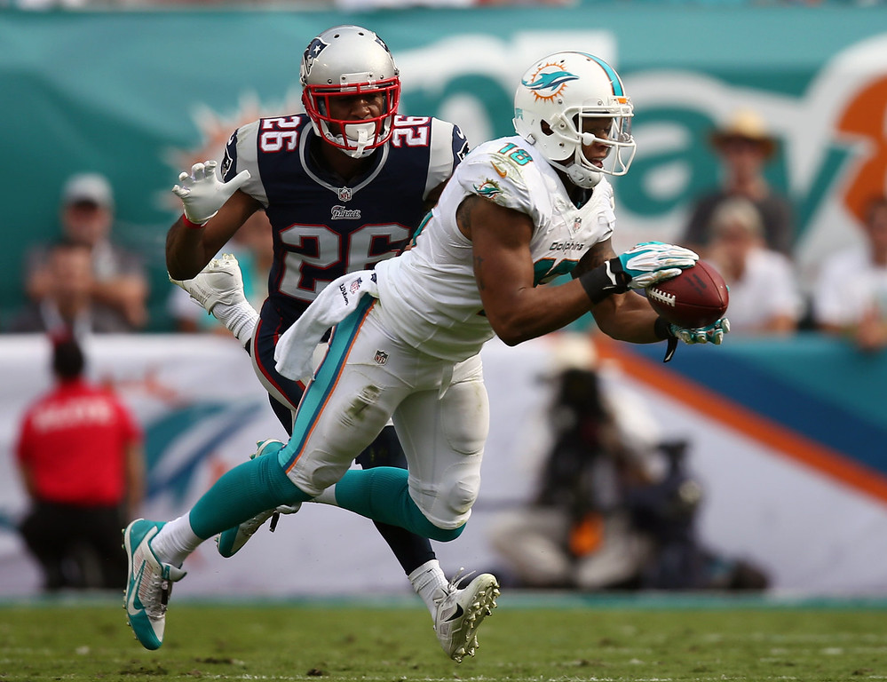 . Miami Dolphins wide receiver Rishard Matthews (18) catches a pass as New England Patriots cornerback Logan Ryan (26) is late with the tackle during the first half of an NFL football game on Sunday, Dec. 15, 2013, in Miami Gardens, Fla. (AP Photo/J Pat Carter)