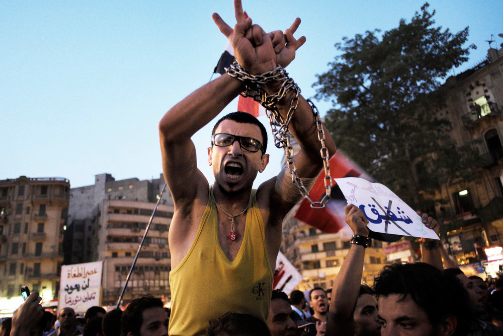. An Egyptian protester raises his chained hands as he shouts slogans against presidential candidate and former premier Ahmed Shafiq during a demonstration in Cairo\'s central Tahrir Square on June 1, 2012. Shafiq, the last prime minister under ousted leader Hosni Mubarak, is to face the Muslim Brotherhood\'s candidate Mohamed Morsi in the second round of Egypt\'s presidential election on June 16-17. MARCO LONGARI/AFP/Getty Images