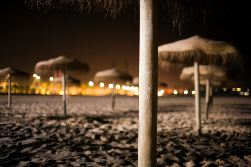 Umbrellas on the beach by night. Town of Sanlucar de Barrameda, province of Cadiz, Andalusia, Spain.