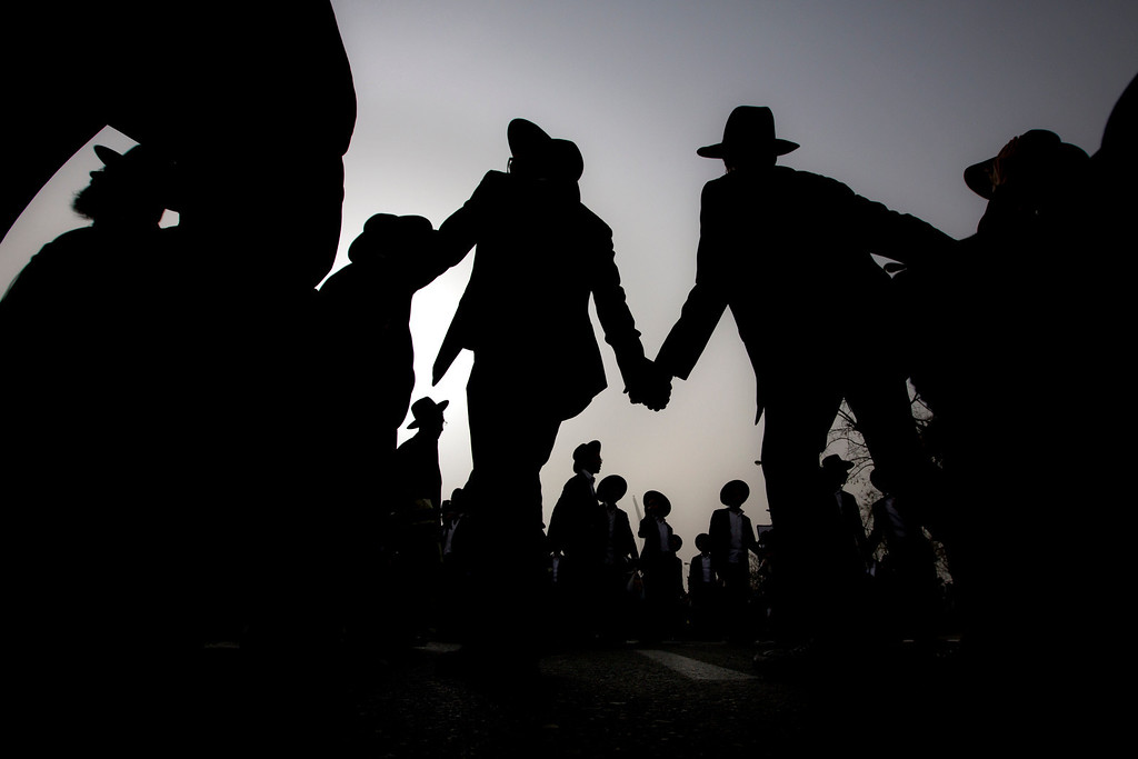 . Ultra-Orthodox Jewish men dance at a rally in a massive show of force against plans to force them to serve in the Israeli military, blocking roads and paralyzing the city of Jerusalem, Sunday, March 2, 2014. The widespread opposition to the compulsory draft poses a challenge to the country, which is grappling with a cultural war over the place of the ultra-Orthodox in Israeli society. With secular Jews required to serve, the issue is one of the most sensitive flashpoints between Israel\'s secular majority and its devout minority. (AP Photo/Sebastian Scheiner)