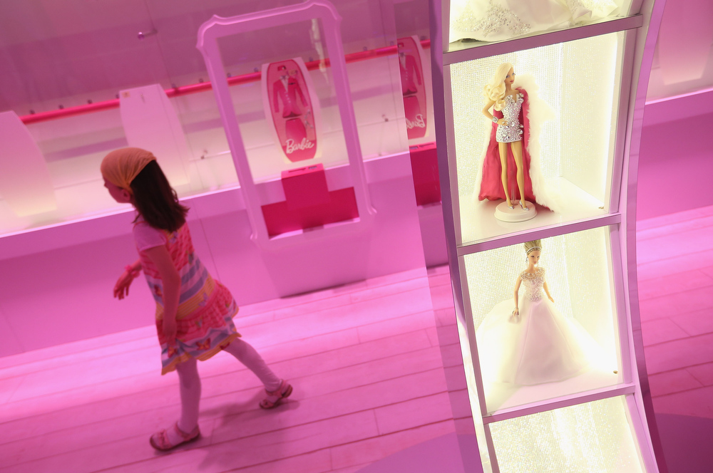. Amalie, 7, walks past Barbie dolls while visiting the Barbie Dreamhouse Experience on May 16, 2013 in Berlin, Germany. The Barbie Dreamhouse is a life-sized house full of Barbie fashion, furniture and accessories and will be open to the public until August 25 before it moves on to other cities in Europe.  (Photo by Sean Gallup/Getty Images)
