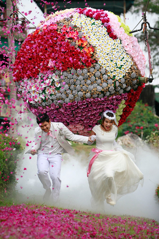 . Prasit Rangsitwong, left, and Varutton Rangsitwong run away from a giant flower ball as a part of an adventure-themed wedding ceremony in Prachinburi province, Thailand, Wednesday, Feb. 13, 2013, on the eve of Valentine\'s Day. (AP Photo/Wason Wanichakorn)
