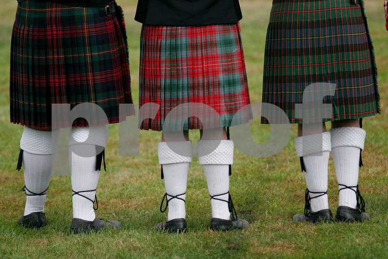 Three Scottish girls watch the Highland Games.