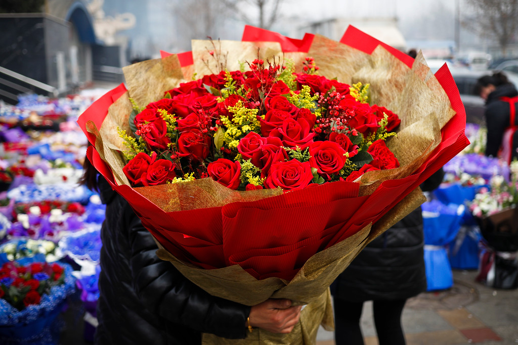 . A woman holds a bouquet of Valentine\'s Day roses at the flower market in Beijing, Tuesday, Feb. 14, 2017. Valentine\'s Day is not a tradition in China but is becoming increasingly popular as Chinese adopt Western customs, encouraged by retailers who see them as a way of boosting sales. (AP Photo/Andy Wong)