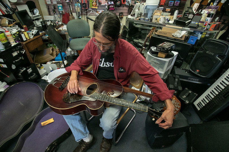 Eddy Troxler the owner of Eddy's Music in Fitchburg shows off the 1918 Gibson U Harp Guitar he just recently got into his shop. Here he tunes the guitar strings on the instrument in his shop on Monday. SENTINEL & ENTERPRISE/JOHN LOVE
