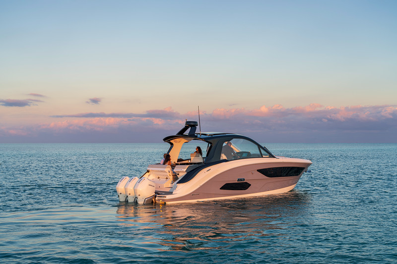 2021-Sundancer-370-Outboard-DAO370-lifestyle-starboard-stern-three-quarter-couple-friends-06070-select.jpg