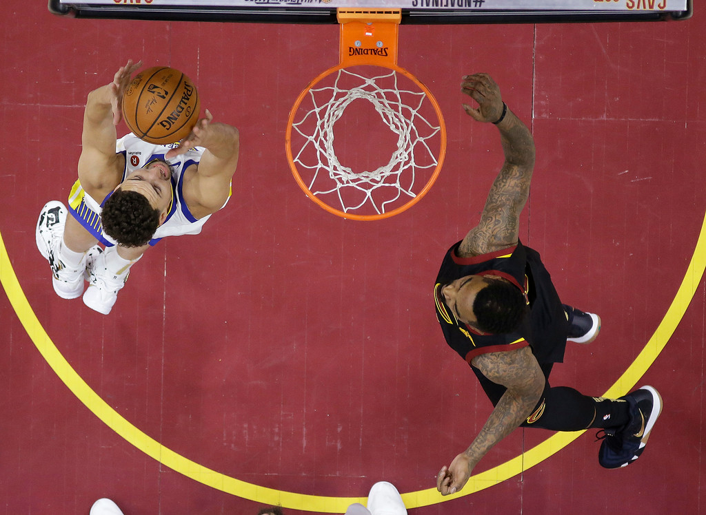 . Golden State Warriors guard Klay Thompson grabs a rebound next to Cleveland Cavaliers guard JR Smith during the first half of Game 4 of basketball\'s NBA Finals, Friday, June 8, 2018, in Cleveland. (AP Photo/Carlos Osorio, Pool)