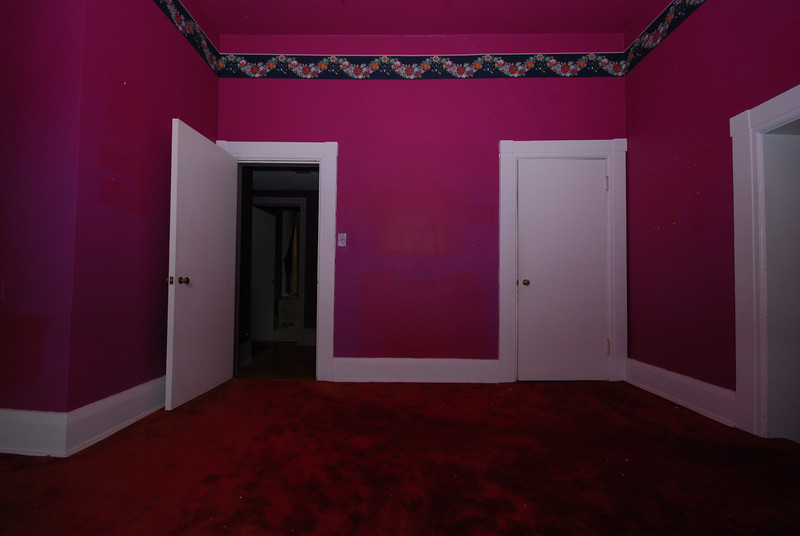 The red bedroom. The door on the left leads to the main hallway (the green bedroom is in the distance). The door at far right steps down to the maid's hallway.