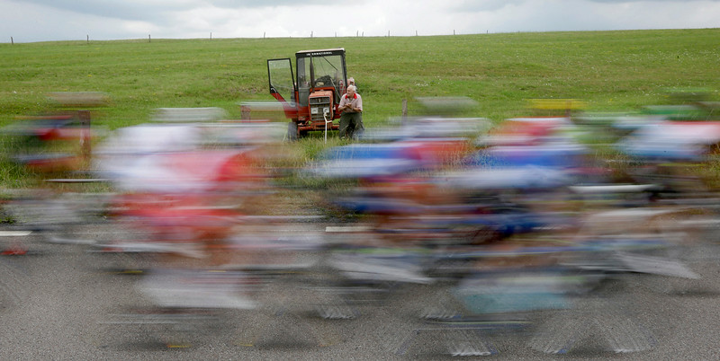 . A farmer sits on the wheel of his tractor as he watches the riders pass during the eighth stage of the Tour de France cycling race over 161 kilometers (100 miles) with start in Tomblaine and finish in Gerardmer, France, Saturday, July 12, 2014. (AP Photo/Laurent Cipriani)