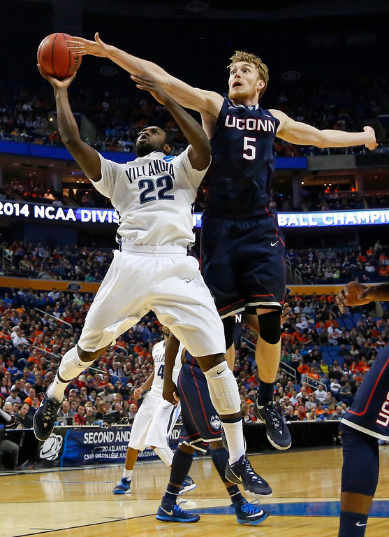 . Villanova\'s JayVaughn Pinkston (22) drives past Connecticut\'s Niels Giffey (5) during the first half of a third-round game in the NCAA men\'s college basketball tournament in Buffalo, N.Y., Saturday, March 22, 2014. (AP Photo/Bill Wippert)
