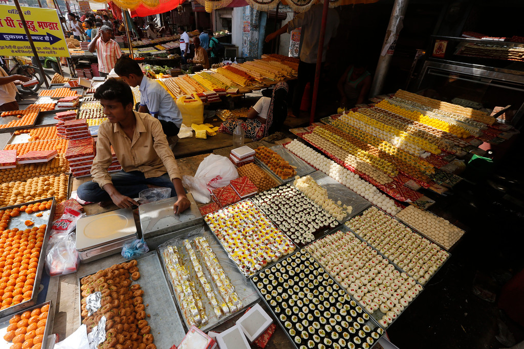 . An Indian vendor displays sweets for sale on Diwali, the festival of lights, in Allahabad, India, Thursday, Oct. 19, 2017. Hindus light lamps, wear new clothes, exchange sweets and gifts and pray to goddess Lakshmi during Diwali, the festival of lights. (AP Photo/Rajesh Kumar Singh)