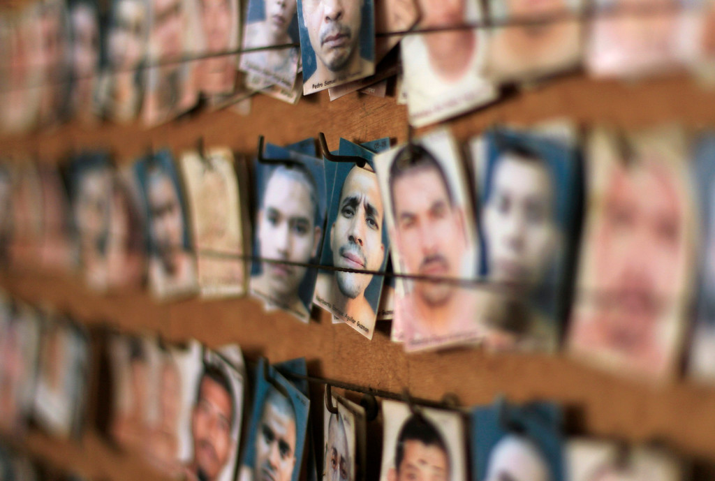 . A board with pictures of jailed gang members is seen at the maximum security jail of Izalco in Sonsonate March 5, 2013. Jailed members of the country\'s two most powerful gangs MS-13 and the 18th Street gang (Mara 18), members of civic organizations and Bishop Fabio Colindres celebrated mass to mark the first anniversary since the two gangs signed a truce in March 2012 in an effort to reduce violent crimes in the country.   REUTERS/Ulises Rodriguez
