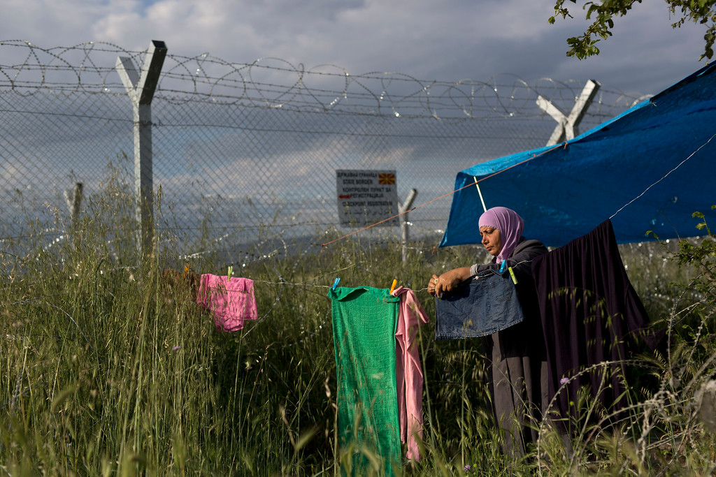 . A woman hungs on his laundery near her tent in front of the wired fence that separate Greece and Macedonia at a makeshift refugee camp on the northern Greek border point of Idomeni, Sunday, May 15, 2016. Thousands of stranded refugees and migrants have camped in Idomeni for months after the border was closed. (AP Photo/Petros Giannakouris)