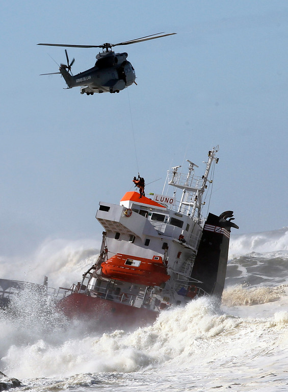 . A sailor is helped lifted off by a military helipcopter  after a Spanish cargo ship that slammed into a jetty in choppy Atlantic Ocean waters off Anglet, southwestern France, Wednesday, Feb. 5, 2014.  (AP Photo/Bob Edme)