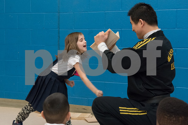 02/22/18 Wesley Bunnell | Staff Master Hyung Yang from Yang's U.S. Taekwondo Academy in Newington gave demonstrations on Thursday 2/22 at Lincoln School which involved teachers and elementary students. First grade student Sarah Salha breaks a board held by Master Yang.