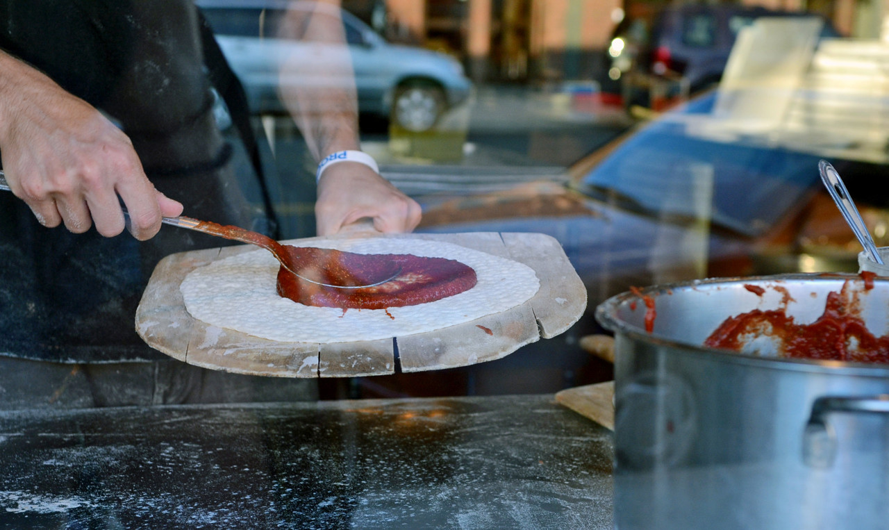 . Vikings fans can put their noses up to the window to watch thick marinara sauce being spooned onto pizza crust at Pagilia\'s Pizza in Mankato. (Pioneer Press: C.J. Sinner)