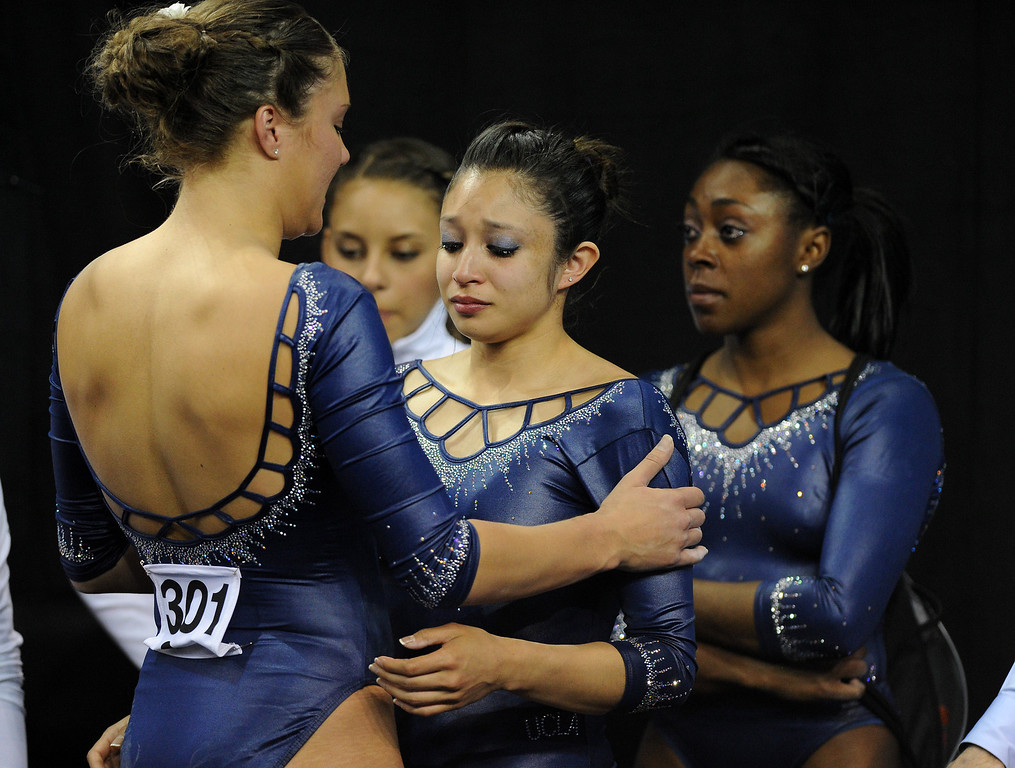 . UCLA\'s Vanessa Zamarripa, center, is comforted by teammate Kaelie Baer, left, after Zamarripa had a bad landing while competing in the vault at the NCAA Women\'s Gymnastics Championship Team Finals at Pauley Pavilion, Saturday, April 20, 2013. (Michael Owen Baker/Staff Photographer)