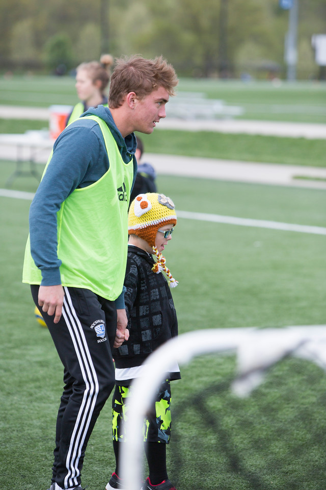 Dixon Glaze, Desoto, 6 (yellow hat) holds Jackson Merckens' hand during a soccer camp for kids with special needs. Jackson is a junior at Rockhurst HS.