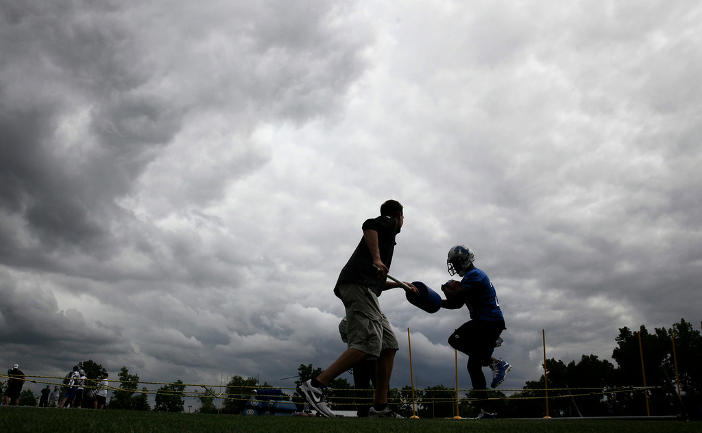. Detroit Lions running back Reggie Bush, right, runs a drill during NFL football training camp in Allen Park, Mich., Monday, July 28, 2014. (AP Photo/Paul Sancya)