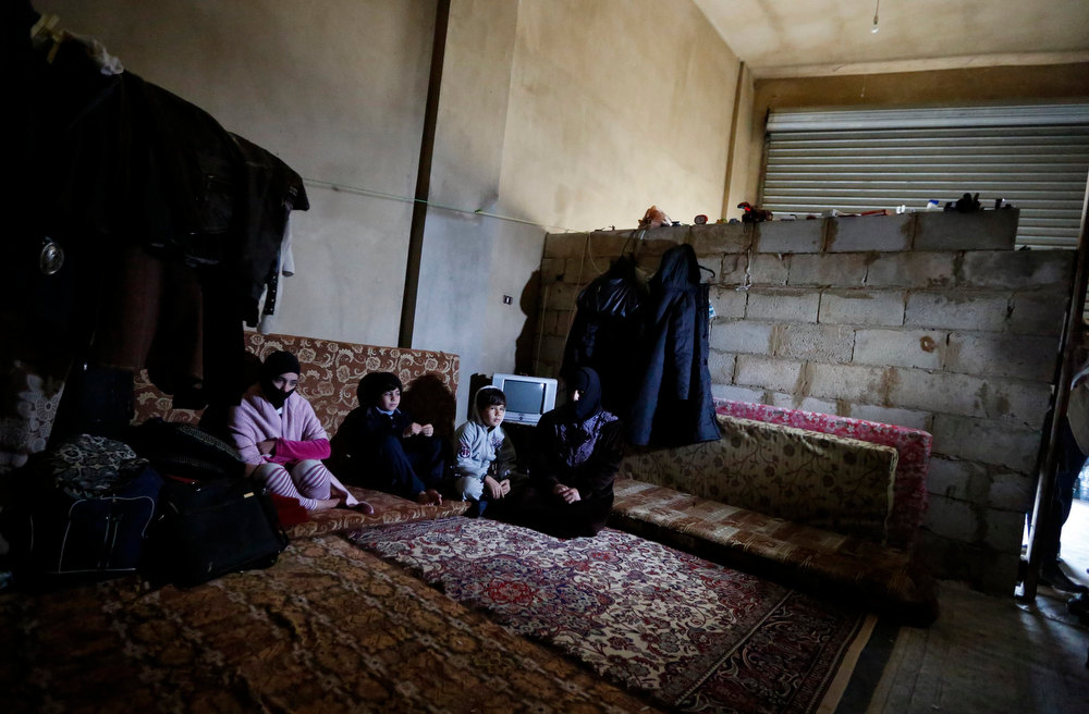 Description of . A Syrian refugee family sit inside the garage where they live in Bar Elias village in the Bekaa valley December 13, 2012. REUTERS/ Jamal Saidi