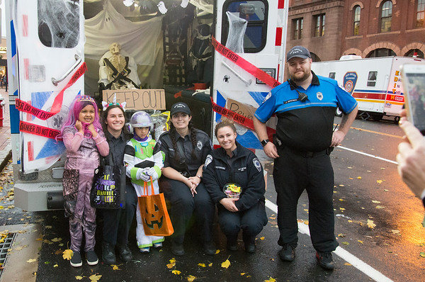 10/31/19 Wesley Bunnell | StaffrrWorkers from New Britain EMS pose with Cecilia Stockey, L, and her brother Brian Stockey during the New Britain Down District Halloween Safe Zone 2019.
