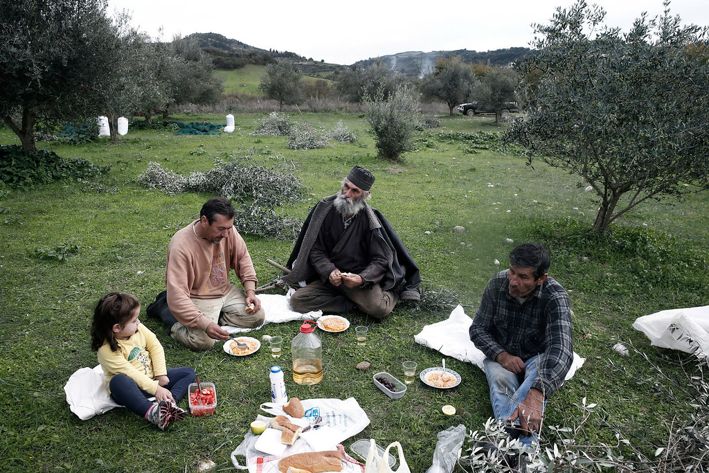 . From left to right, Asimina Nikolopoulou, Tasos Nikolopoulos, Greek Orthodox Priest Dimitris Vlasopoulos, and Yiannis Nikolopoulos, have a picnic in an olive grove in Kalo Pedi village, about 335 kilometers (210 miles) west of Athens, Greece on Friday, Nov. 29, 2013. Widespread ownership of olive groves among Greeks has helped maintain supplies to households as they struggle through a sixth year of recession. (AP Photo/Petros Giannakouris)