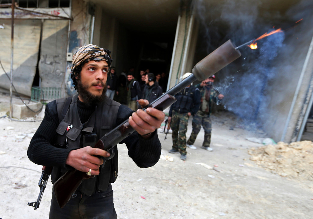 . A Free Syrian Army fighter uses a shotgun to fire a homemade grenade at Syrian Army soldiers during a fight in Arabeen neighborhood of Damascus January 24, 2013.   REUTERS/Goran Tomasevic
