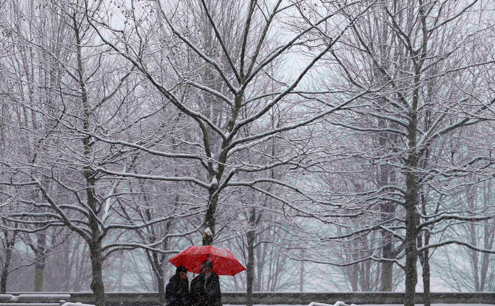 Description of . A couple walks along a path in Millennium Park during a snowstorm in Chicago March 5, 2013. A deadly late winter storm dumped heavy snow on the Midwestern United States on Tuesday, contributing to numerous highway crashes and flight cancellations as it moved east toward the Ohio Valley and the mid-Atlantic states.  REUTERS/Jim Young