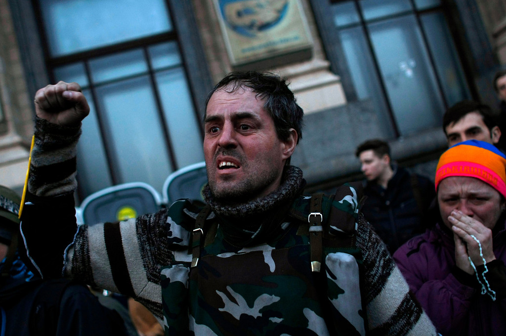 . A man clenches his fist during a funeral procession for anti-government protesters killed in clashes with the police at Independence Square in Kiev, Ukraine, Friday, Feb. 21, 2014.  (AP Photo/ Marko Drobnjakovic)
