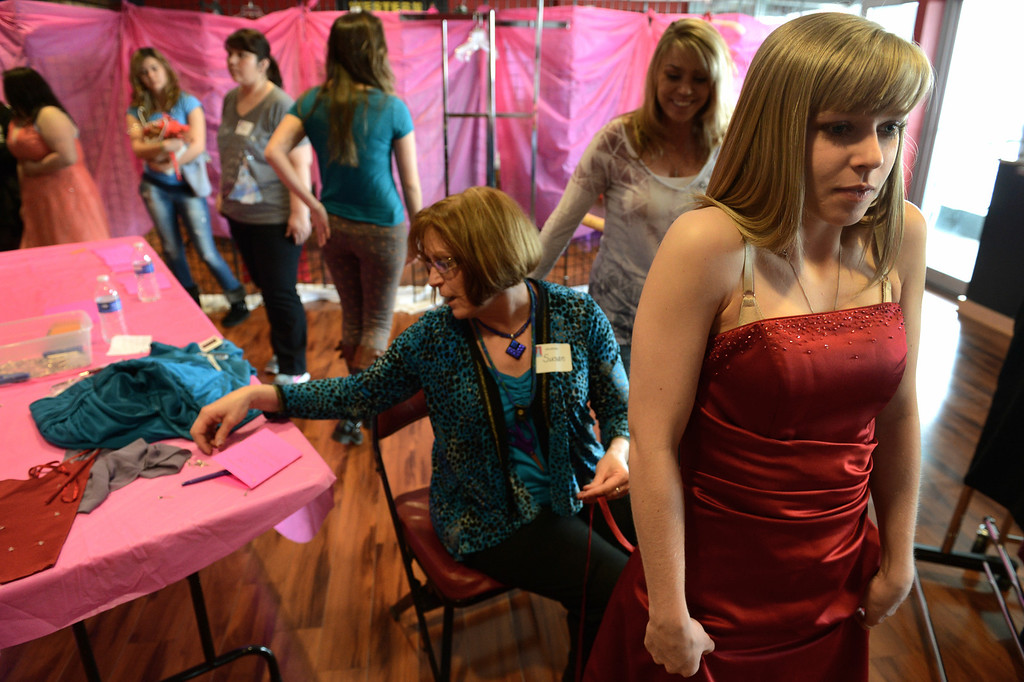 """. COMMERCE CITY, CO. - MARCH 16: Kersey Ruder, a senior at Green Mountain High School,   admires her dress while having alterations made by Susan Nixon during the Prom Dress Exchange Corp. event in Commerce City, CO March 16, 2013. With a valid student ID and a suggested $10 donation, teenage girls could chose from 1,356 donated dresses that lined a long hallway at Dick�s Sporting Goods Park.   Kersey\'s mother, Valerie Ruder, second from right, said, \""""it\'s amazing. The girls can get a beautiful dress and not spend a million dollars. I love that they volunteer for alterations... they\'re kind people.\"""" (Photo By Craig F. Walker/The Denver Post)"""