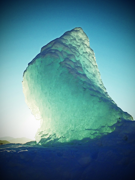 An illuminated iceberg on the frozen Mendenhall Lake near Mendenhall Glacier in Juneau, Alaska