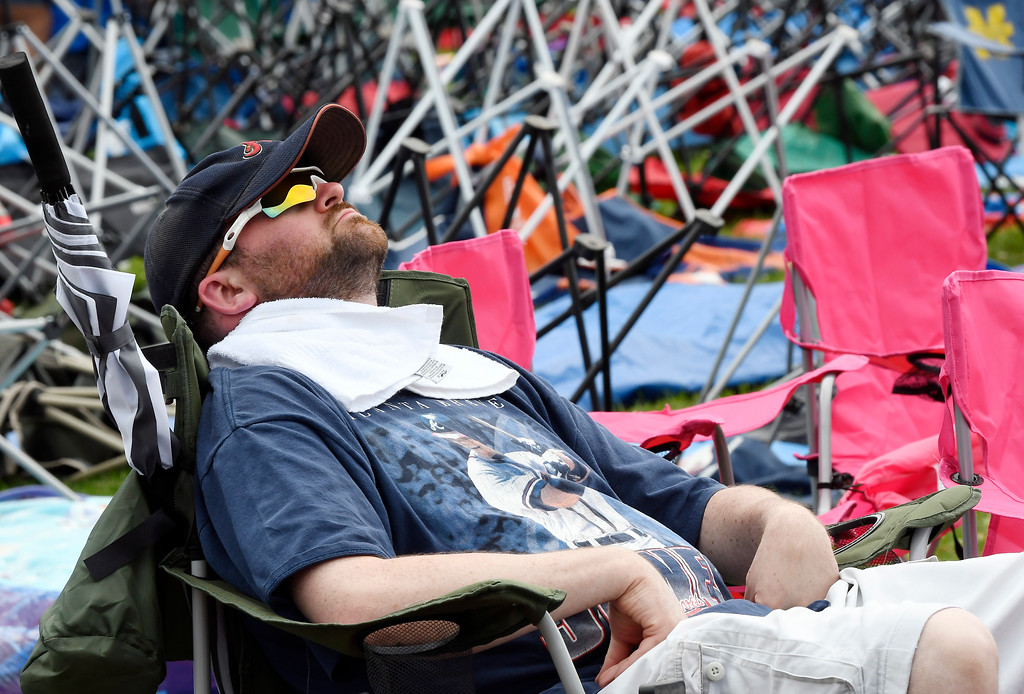 . Chipper Jones fan Alex French, of Aurora, Mo., takes a nap before the start National Baseball Hall of Fame induction ceremonies Sunday, July 29, 2018, in Cooperstown, N.Y. (AP Photo/Hans Pennink)