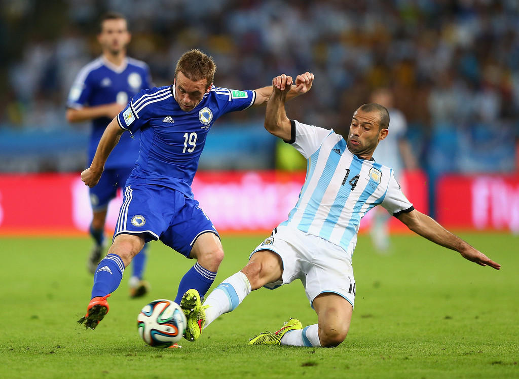 . Javier Mascherano of Argentina challenges Edin Visca of Bosnia and Herzegovina during the 2014 FIFA World Cup Brazil Group F match between Argentina and Bosnia-Herzegovina at Maracana on June 15, 2014 in Rio de Janeiro, Brazil.  (Photo by Jamie Squire/Getty Images)
